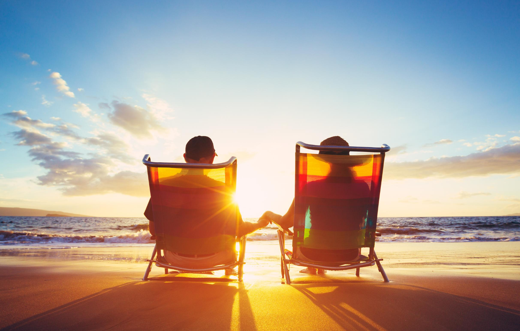 How to boost your superannuation. Middle age couple sitting on beach chairs facing the sunset and holding hands.