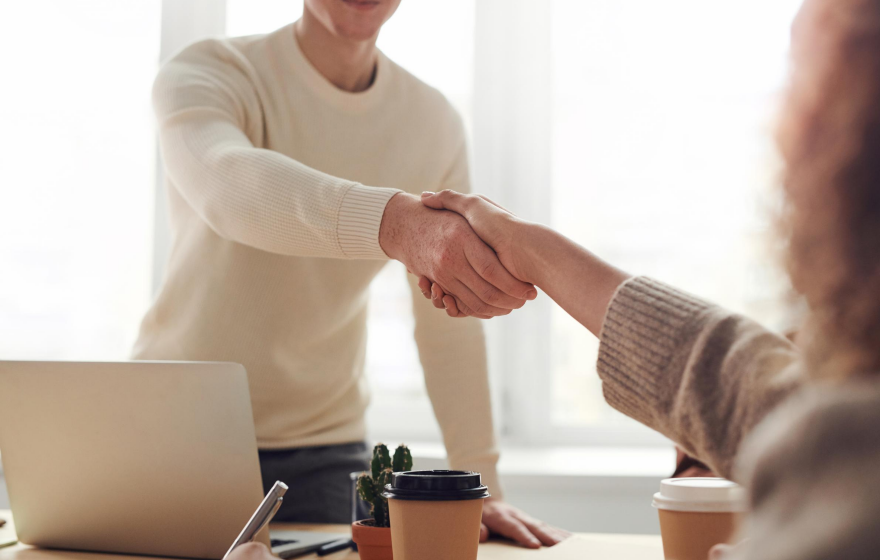 How to choose your business structure. Close up shot of young man shaking hand of young woman over an office desk.