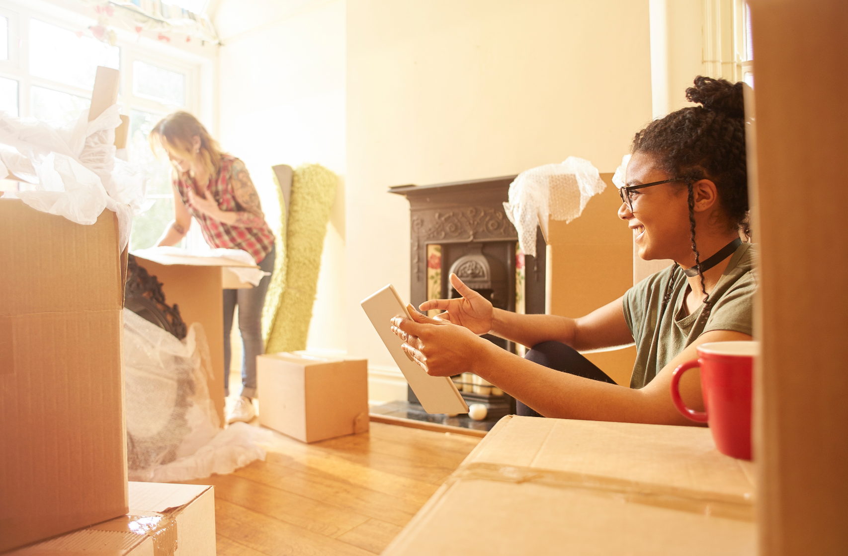 Two young girls unpacking cardboard boxes after buying their first home.